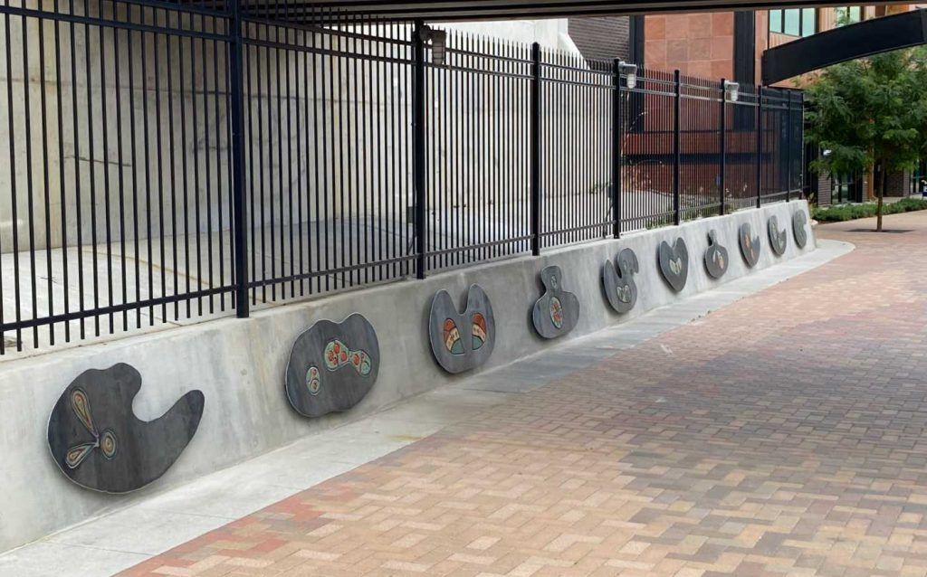 """The north wall of the underpass with ten panels spelling """"Louisville"""""""