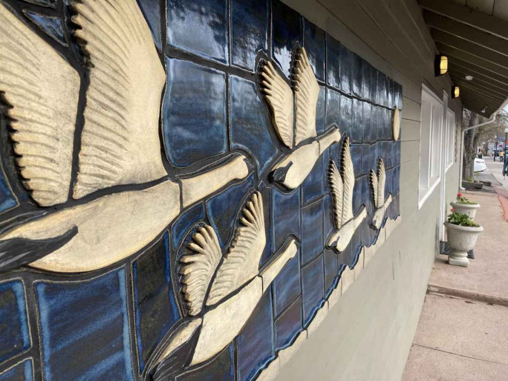 """Side view of """"Trumpeter Swans"""" - a ceramic mural by Gregory Fields"""