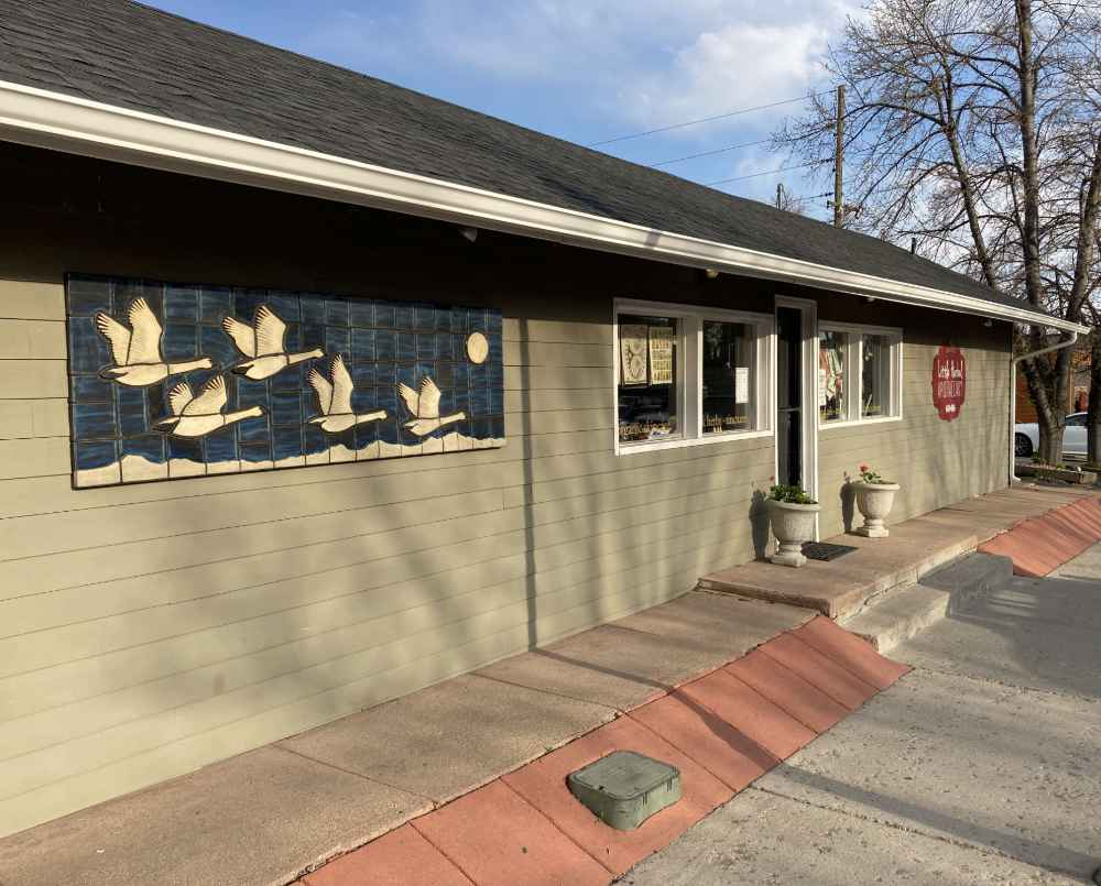 """The """"Trumpeter Swans"""" ceramic mural by Gregory Fields on the side of the Little Herbal Apothecary in Lafayette, Colorado"""