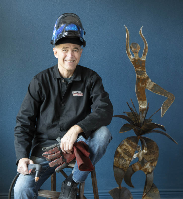 Gregory Fields sitting on a stool in welding gear, next to one of his steel sculptures